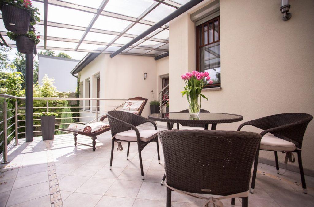 Gestaltet man den balkon als moderne Terrasse, können dort mediterrane Fliesen zum Einsatz kommen. Gegen überraschenden regen schützt das Glasdach.