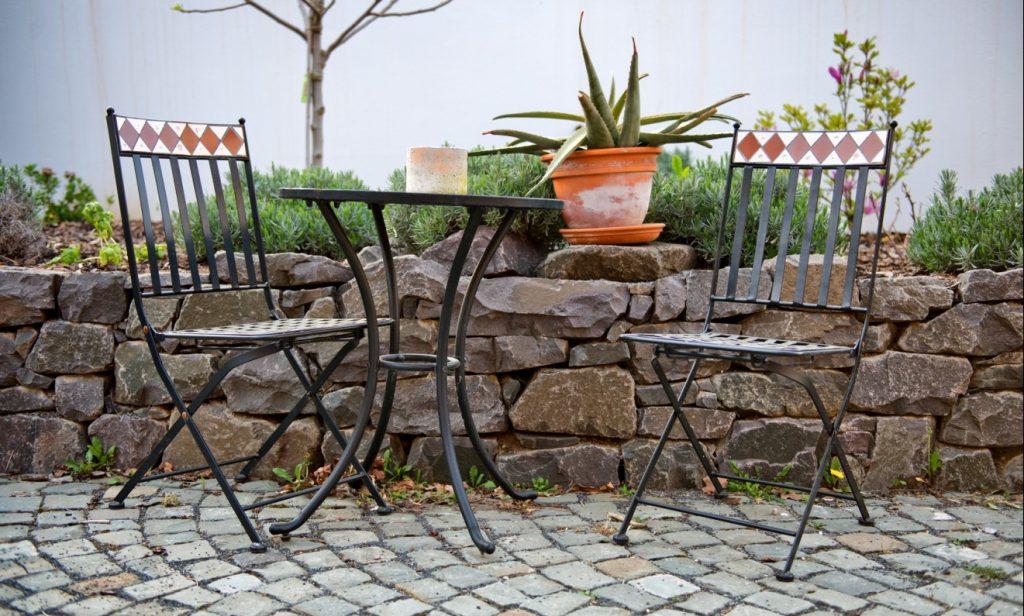6. Schmiedeeiserne Sitzgarnitur auf Kopfsteinpflaster im Steingarten