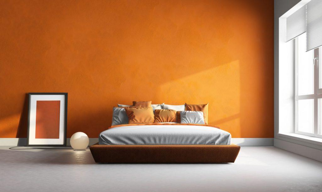 7. Mal Wandfarben-Ideen: Orangefarbene Wand dominiert den Raum
