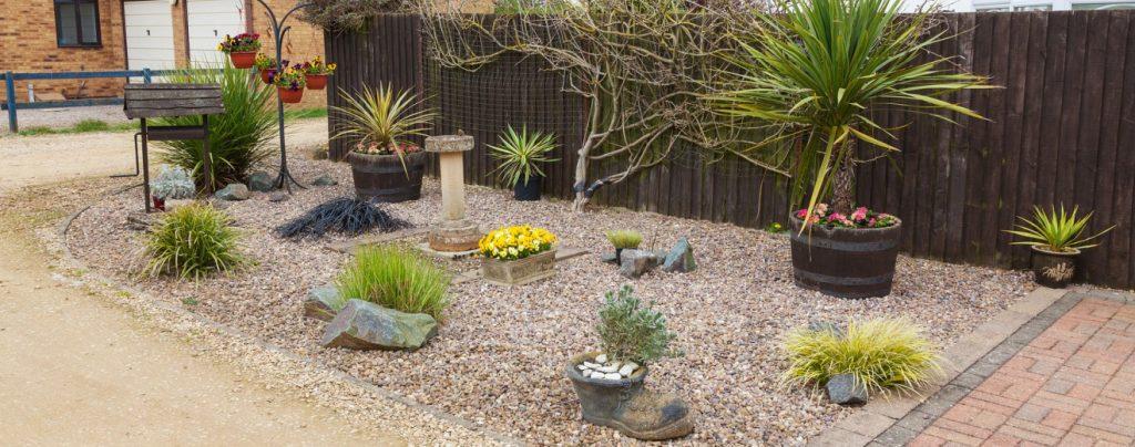8. Steingarten als Willkommensbereich mit Stiefmütterchen, Yucca-Palme und feinen Gräsern