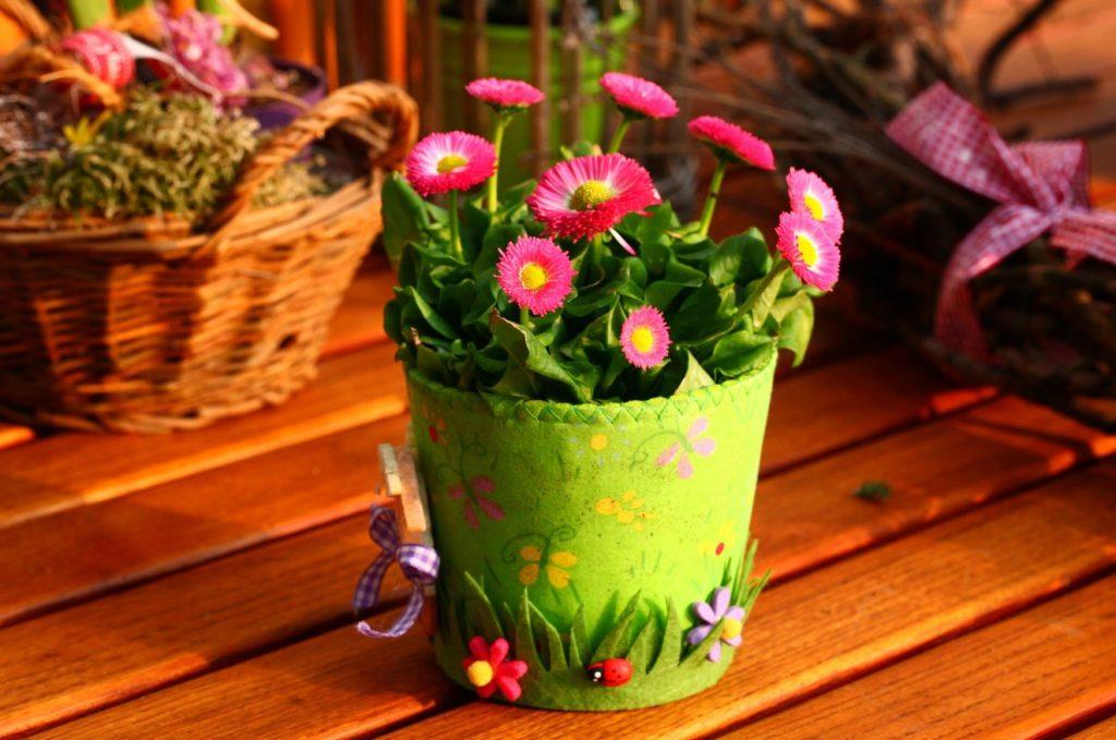 Ein kleiner Garten braucht Sitzgelegenheiten. Wie wäre es mit einer hölzernen Parkbank, die Sie mit bunten Blumentöpfen verzieren?