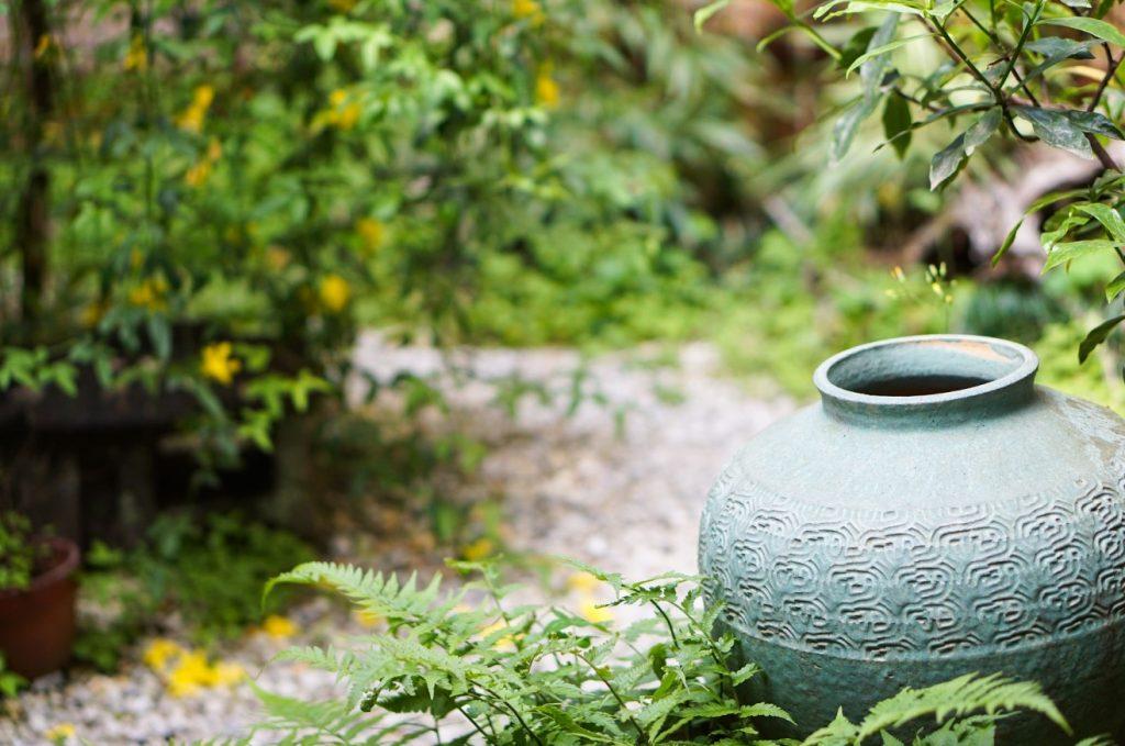 Vasen und Amphoren am Wegesrand geben einem kleinen Garten Tiefe und romantische Verträumtheit