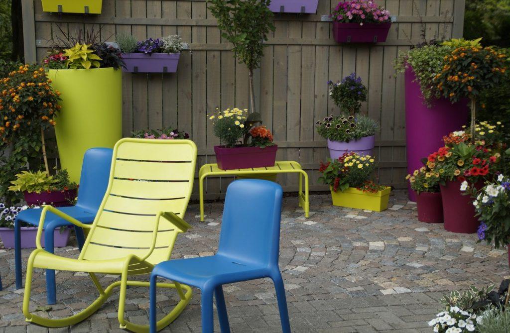 8. Idee: Terrasse mit bunten Planzkübeln und Blumen auf Kopfsteinpflaster