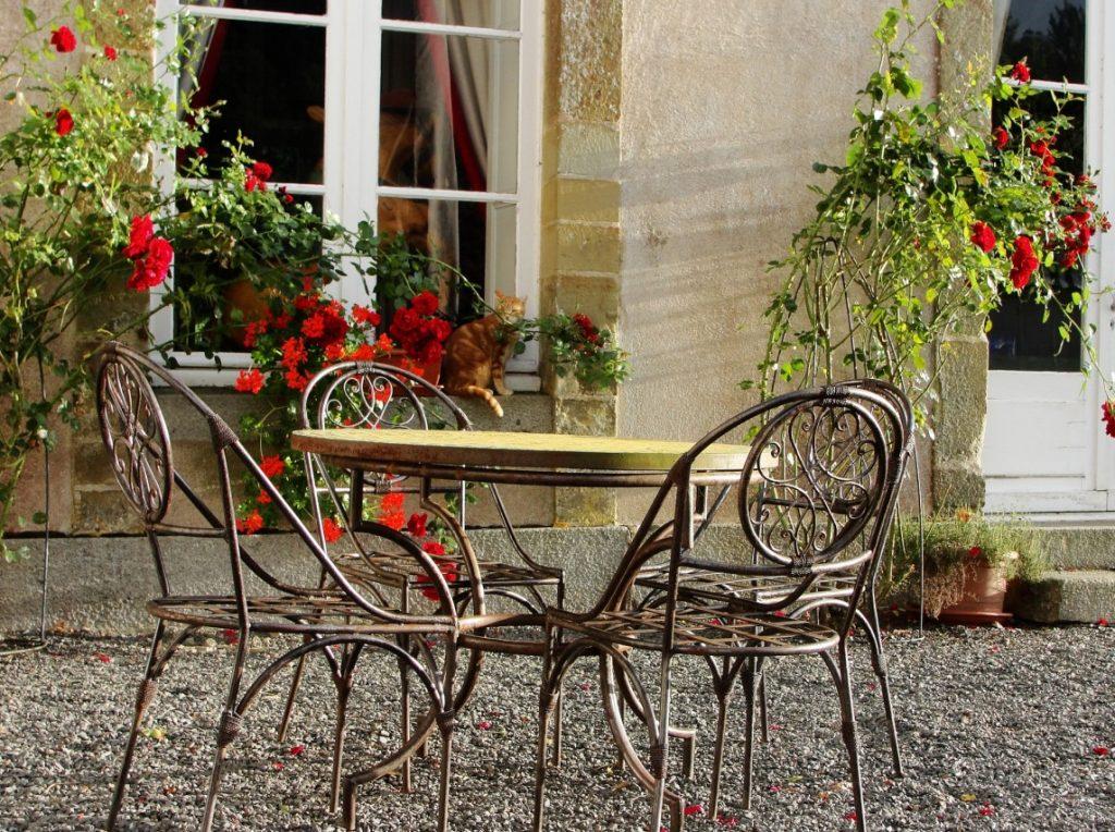 Tipp #2: Stahlrohr-Sitzmöbel auf Kies vor einem Rosenspalier wie vor einem französischen Chateau