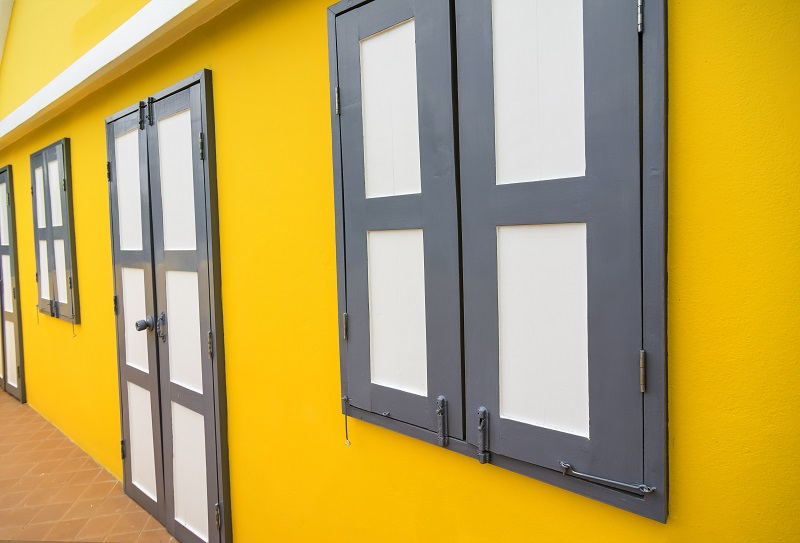 Gelb, gelb, gelb ist die komplette Fassade. Im Kontrast dazu die Türen und Fenster in ruhigen, gedeckten Farben. (#06)