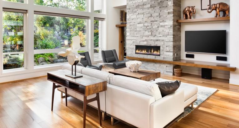 Bodentiefe Fenster zaubern besonders viel Licht und lassen das Wohnzimmer offen und modern wirken. Ein Kamin erhöht den Gemütlichkeitsfaktor und bringt Wärme an kalten Tagen. (#3)