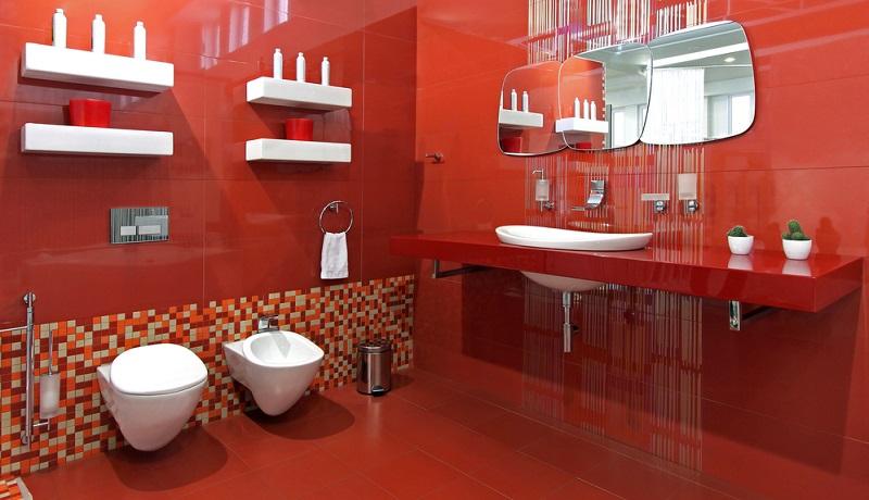 Glänzende, rote Keramikfliesen verkleiden den Boden und die Wände, wobei der untere Bereich einer Wand mit einer breiten Bordüre aus kleinen quadratischen Fliesen in verschiedenen Rottönen und Beige verziert wurde.