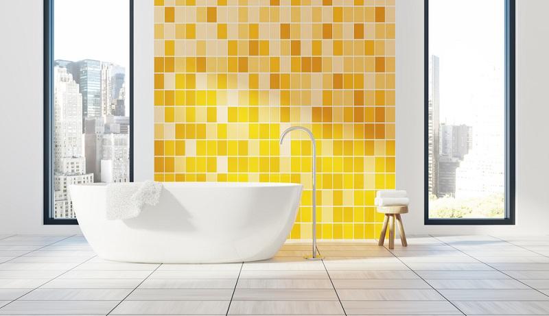 Bodentiefe Fenster und eine Wand, die in verschiedenen Gelbtönen gefliest ist, bilden den optischen Rahmen dieses schönen Badezimmers.