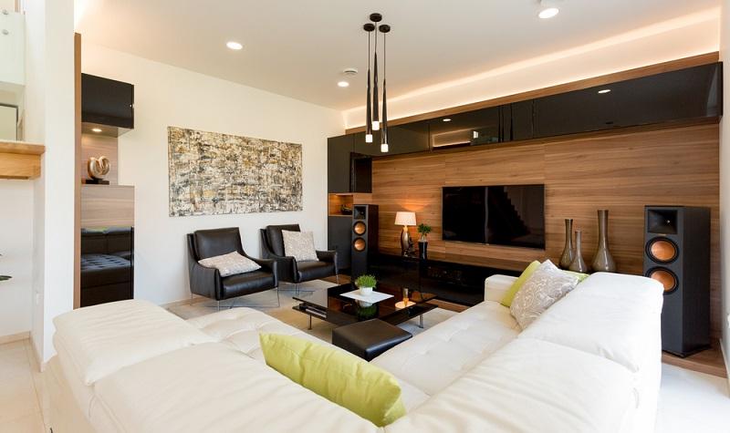 Dieses Wohnzimmer vereint helle und dunkle Farbtöne ebenso wie das schwere Design der dunklen Wohnwand mit den filigranen Deckenleuchten. ( Foto: Shutterstock-JRP Studio )